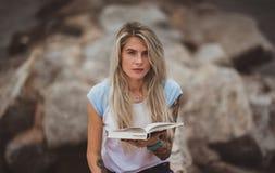 美丽的白肤金发的妇女坐一个石堤防和读书 被刺字的手 现代,时髦,学生 库存图片