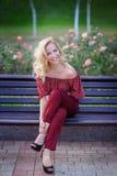 美丽的白肤金发的妇女坐一条长凳在公园 免版税图库摄影