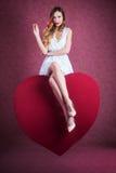 年轻美丽的白肤金发的妇女坐巨型心脏 库存照片