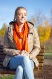 美丽的白肤金发的妇女坐长凳在秋天公园 图库摄影