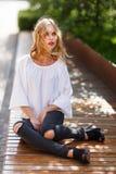 美丽的白肤金发的妇女坐长凳,微风翻动了她的头发 免版税图库摄影