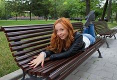 美丽的白肤金发的妇女坐长凳 免版税图库摄影