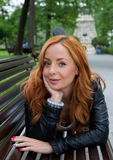 美丽的白肤金发的妇女坐长凳 免版税库存照片