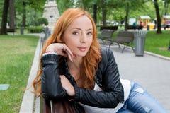 美丽的白肤金发的妇女坐长凳 免版税库存图片