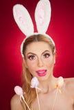 美丽的白肤金发的妇女当与室内天线的复活节兔子在红色背景,演播室射击 拿着三个色的鸡蛋的小姐 免版税库存图片