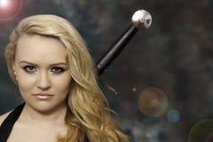 年轻美丽的白肤金发的妇女或女孩有一把剑的在后面后 免版税库存图片