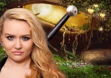 美丽的白肤金发的妇女或女孩有一把剑的在bac后 库存图片