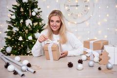 美丽的白肤金发的妇女打开的圣诞礼物在客厅 免版税库存图片