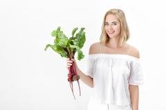 美丽的白肤金发的妇女拿着与绿色叶子的甜菜根在白色背景 健康和维生素 免版税库存图片