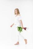 美丽的白肤金发的妇女拿着与绿色叶子的甜菜根在白色背景 健康和维生素 库存照片