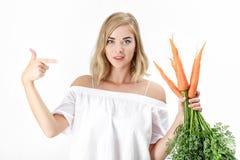 美丽的白肤金发的妇女显示与绿色叶子的一棵新鲜的红萝卜在白色背景 饮食健康 免版税库存图片