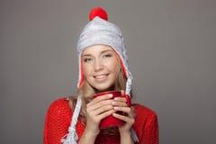 美丽的白肤金发的妇女用一份芳香热的咖啡在手上 免版税库存图片