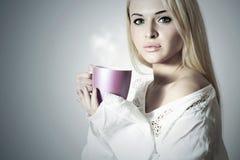 美丽的白肤金发的妇女用咖啡或茶。热的饮料杯 免版税图库摄影