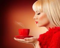 美丽的白肤金发的妇女用咖啡 免版税库存照片
