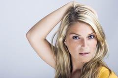 美丽的白肤金发的妇女用她的对她的头发的手 库存照片