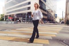 美丽的白肤金发的妇女用去的咖啡穿过路 免版税库存图片