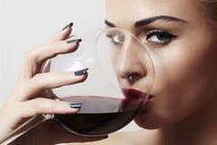 美丽的白肤金发的妇女用wineglass.red lips.dry红葡萄酒 免版税图库摄影