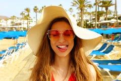 美丽的白肤金发的妇女画象有草帽和太阳镜的获得乐趣在海滩 滑稽的梦中情人在她的暑假 免版税库存照片