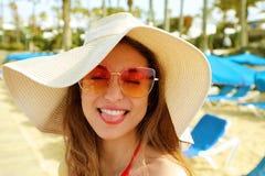 美丽的白肤金发的妇女画象有草帽和太阳镜的获得乐趣在海滩 滑稽的梦中情人在她的暑假 免版税图库摄影