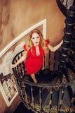 美丽的白肤金发的妇女红色紧身的礼服 免版税库存图片