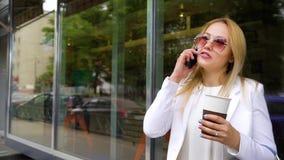 美丽的白肤金发的妇女谈话在拿着在街道上的手机咖啡杯 影视素材