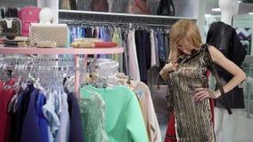 美丽的白肤金发的妇女选择在精品店的衣裳 股票录像