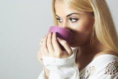美丽的白肤金发的妇女饮用的咖啡。蒸气茶 免版税库存图片