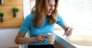 美丽的白肤金发的妇女饮用的咖啡和读新闻 库存图片