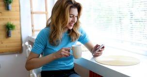 美丽的白肤金发的妇女饮用的咖啡和读新闻 免版税库存图片