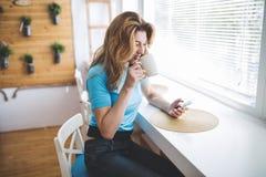 美丽的白肤金发的妇女饮用的咖啡和读新闻 免版税库存照片