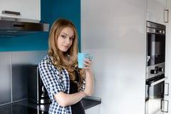 美丽的白肤金发的妇女饮用的咖啡在厨房里 免版税库存照片