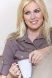 美丽的白肤金发的妇女饮用的茶或咖啡在家 免版税库存图片