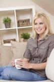 美丽的白肤金发的妇女饮用的茶或咖啡 免版税库存图片