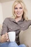 美丽的白肤金发的妇女饮用的茶或咖啡 库存照片