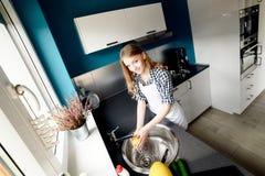 美丽的白肤金发的妇女洗盘子 库存图片