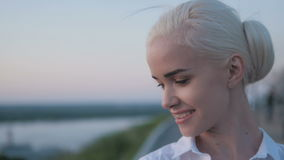 年轻美丽的白肤金发的妇女画象在城市,微笑在日落 库存图片
