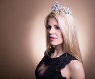 年轻美丽的白肤金发的妇女画象黑礼服和冠的 图库摄影