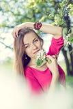 美丽的白肤金发的小姐俏丽的女孩的图片有站立在开花的树下&看照相机的蓝眼睛的 库存图片