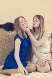 2美丽的白肤金发的少妇、姐妹或者最佳的俏丽的女朋友获得乐趣在戏弄的床愉快微笑的放松 免版税库存图片