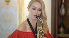美丽的白肤金发的少妇弹萨克斯管 红色礼服的性感的女孩在家演奏萨克斯管或党,坐椅子 股票录像