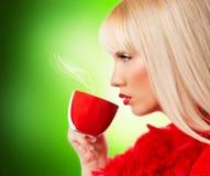 美丽的白肤金发的少妇用咖啡或茶 免版税库存图片
