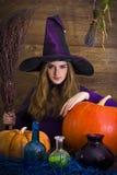 美丽的白肤金发的巫婆在与笤帚的紫色万圣夜 免版税图库摄影