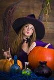 美丽的白肤金发的巫婆在与笤帚的紫色万圣夜 免版税库存照片