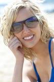 美丽的白肤金发的微笑的太阳镜妇女&# 免版税库存图片