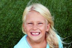 美丽的白肤金发的微笑的女孩坐草在一个夏日 免版税库存图片