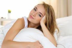 年轻美丽的白肤金发的微笑的妇女画象叫醒早期的早晨 免版税库存图片