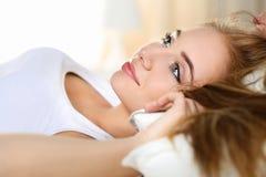年轻美丽的白肤金发的微笑的妇女画象叫醒早期的早晨 免版税库存照片