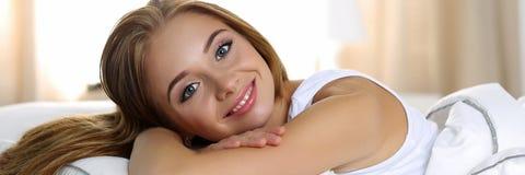 年轻美丽的白肤金发的微笑的妇女画象叫醒早期的早晨 免版税图库摄影