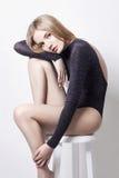 美丽的白肤金发的性感的妇女 有完善的身体的女孩坐凳子 美好的长的头发和腿,光滑的干净的皮肤,护肤 免版税库存照片