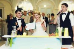 美丽的白肤金发的拿着婚礼certif的新娘和英俊的新郎 免版税库存图片